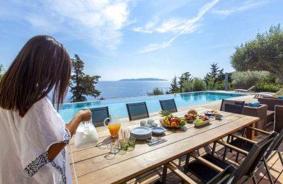 villa-aurora-lefkada-lefkas-afteli-outdoor-breakfast-table-girl-37a1wk55ao6gn730tu2pl6