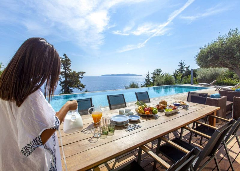 villa-aurora-lefkada-lefkas-afteli-outdoor-breakfast-table-girl-37a1wk55ao6gn730tu2pl6