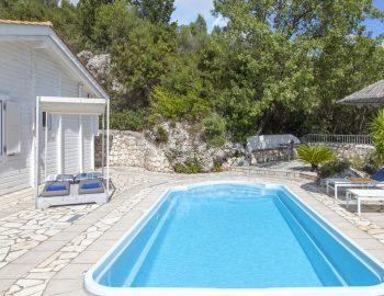 vasiliki-cottages-villa-afteli-lefkada-greece-pool-area-with-lush-green-garden