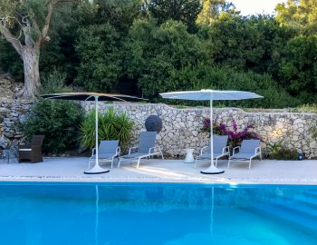 villa-amadeus-poros-lefkada-greece-private-pool-area-with-sunbeds-and-umbrellas